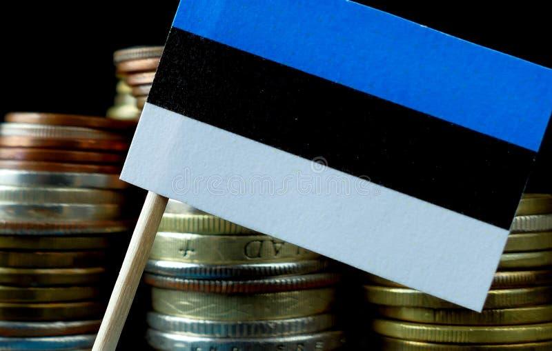 Estlandse vlag die met stapel geldmuntstukken golven stock afbeelding