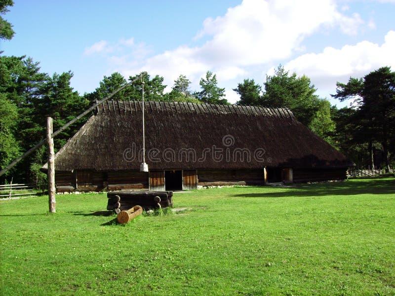 Estnisches Landhaus des alten Strohdachs mit Brunnen lizenzfreie stockfotos