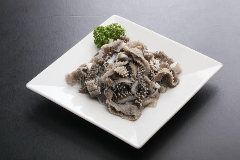 Estomac cuit au four de vache à troisième estomac avec des herbes de cumin sur le plateau blanc photos stock