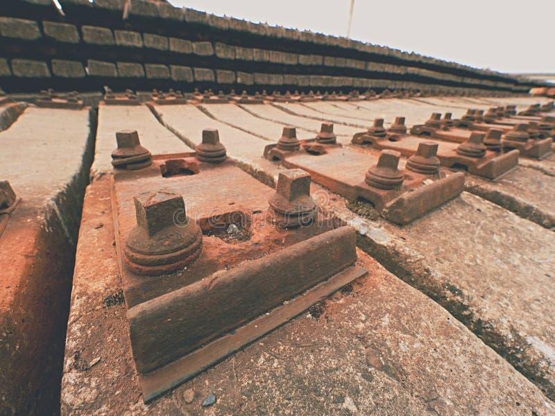 Estoque usado dos dorminhocos no depósito railway Laços railway concretos usados velhos, sujos e oxidados armazenados imagem de stock