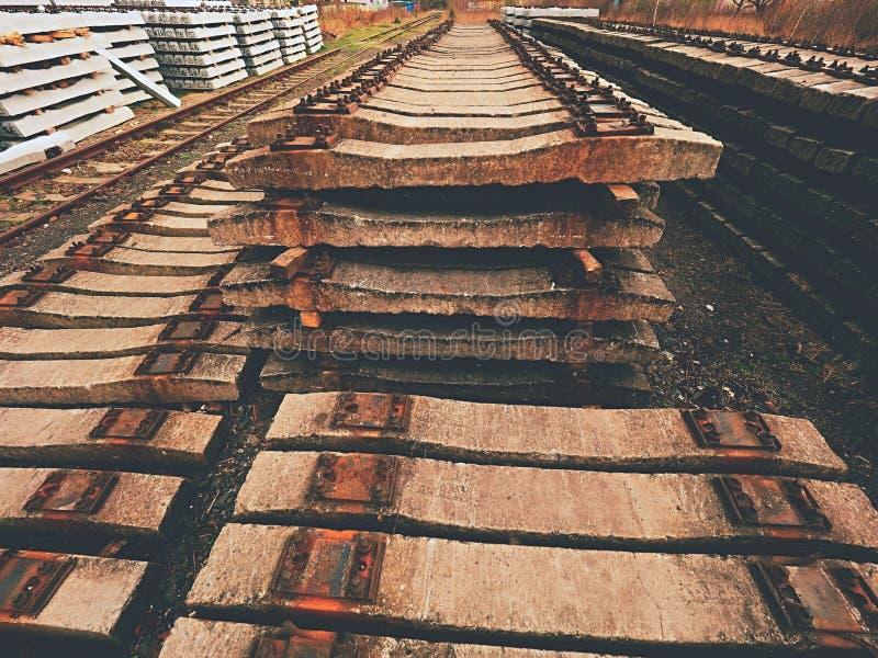 Estoque usado dos dorminhocos no depósito railway Laços railway concretos usados velhos, sujos e oxidados armazenados foto de stock royalty free