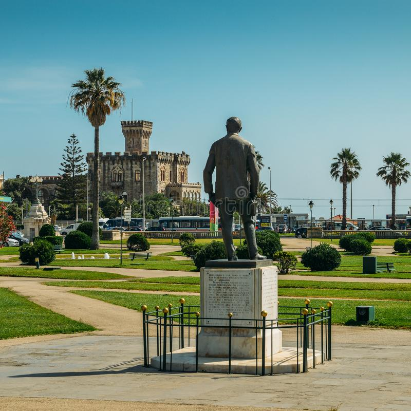 Statue of Fausto Cardoso and Baronial Estoril Castle in background overlooking the ocean. Estoril, Portugal - August 30, 2018: Statue of Fausto Cardoso and stock photo