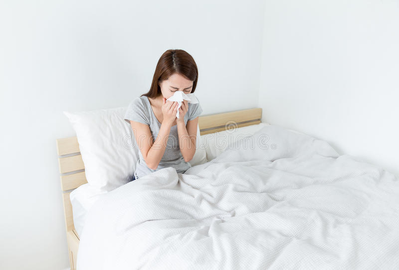 Estornudo de la mujer en la cama imagenes de archivo