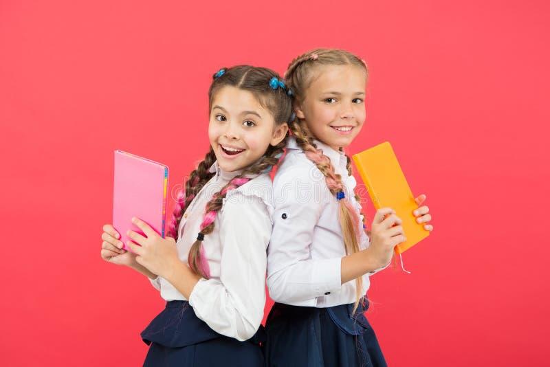 Estos libros son absolutamente genio Pequeños niños del genio que sonríen en fondo rojo Muchachas del genio o niños felices de la imagenes de archivo