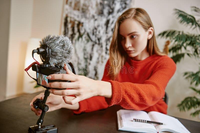Estoy casi listo Retrato del blogger femenino serio que pone su cámara digital montada trípode antes de hacer un nuevo imagen de archivo libre de regalías
