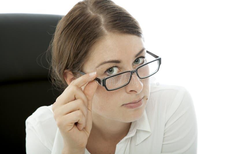 Estrabismo triguenho novo da mulher de negócio sobre vidros fotografia de stock