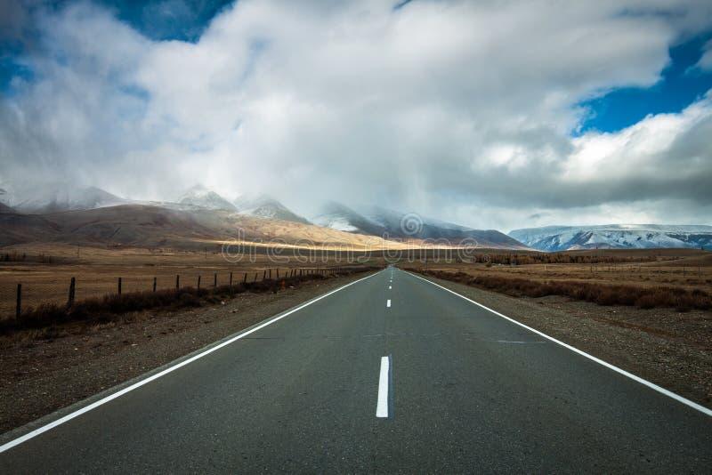 A estrada à esquerda é uma cordilheira acima de que as nuvens acumularam e está nevando imagens de stock royalty free