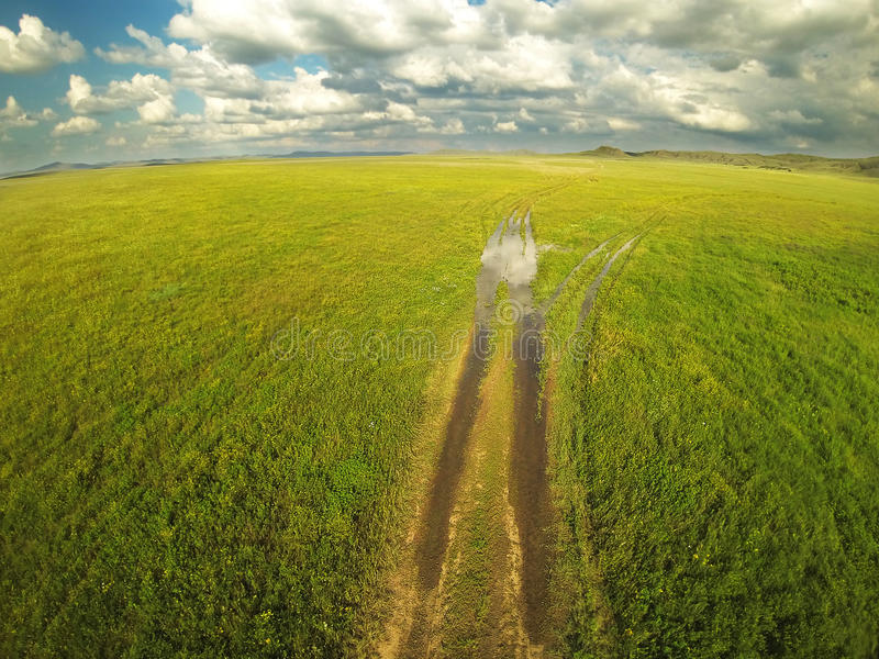 Estrada à terra e céu nebuloso nos estepes de Cazaquistão Montanha aérea de Photography imagens de stock royalty free