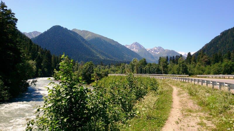 Estrada às montanhas contra o céu fotos de stock
