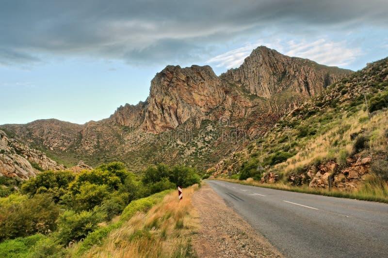 Estrada às montanhas no crepúsculo imagens de stock royalty free