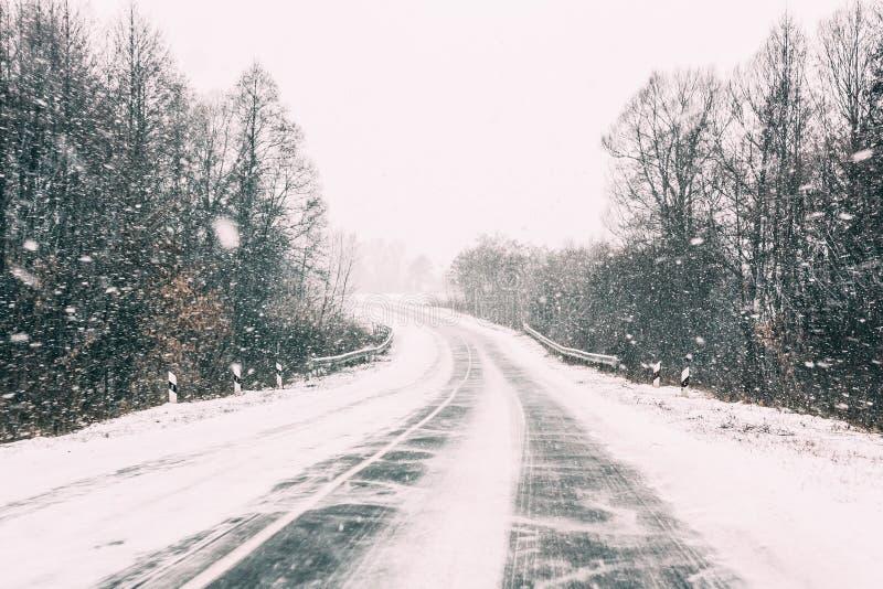 Estrada aberta coberto de neve durante uma tempestade de neve do inverno Tempo adverso fotografia de stock royalty free