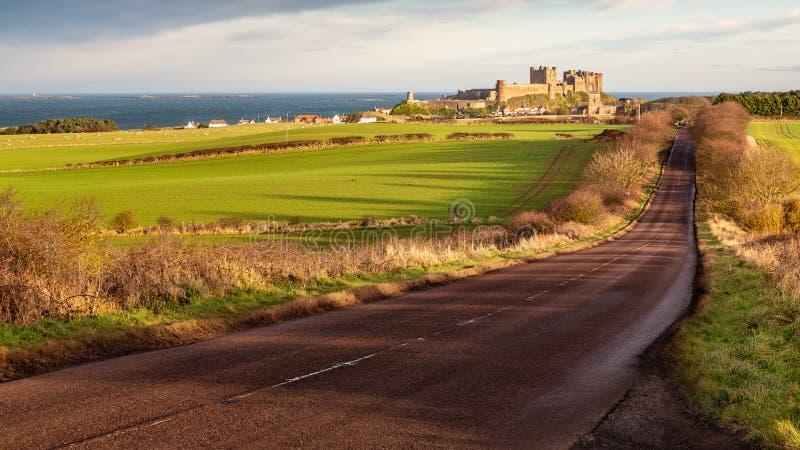 A estrada ao castelo de Bamburgh imagens de stock