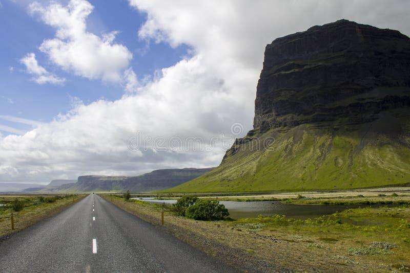 A estrada ao lado das montanhas imponentes de Islândia fotos de stock