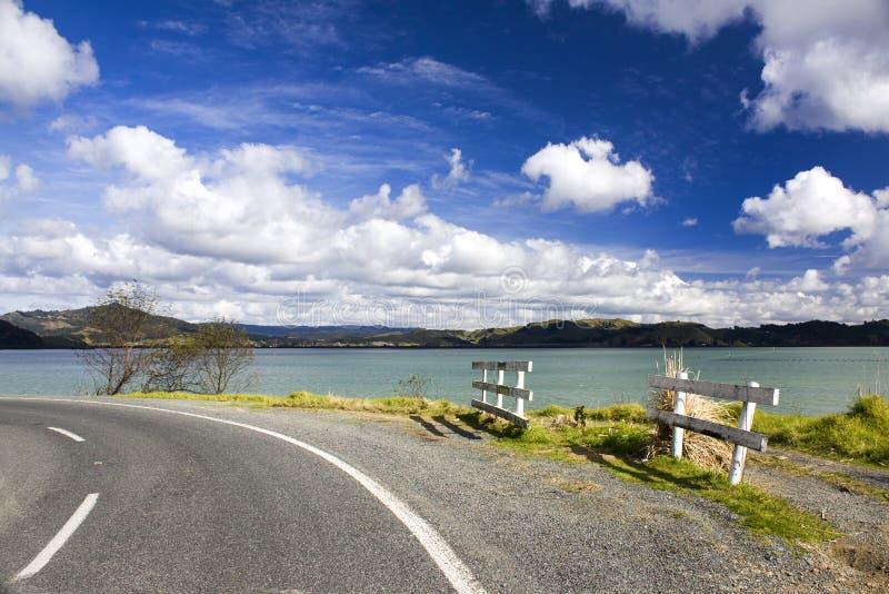 Estrada ao longo de um lago com as nuvens brancas acima dele imagens de stock