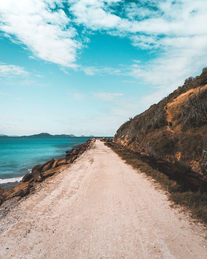 Estrada arenosa estreita que vai ao lado do mar e dos montes íngremes altos com um céu azul nebuloso bonito imagem de stock royalty free