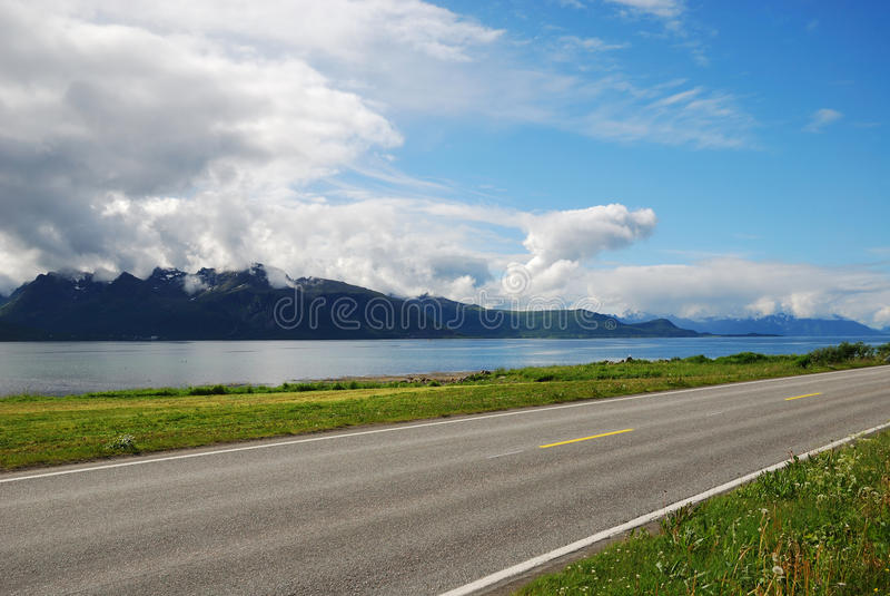 Estrada asfaltada ao longo do fiorde azul. imagem de stock