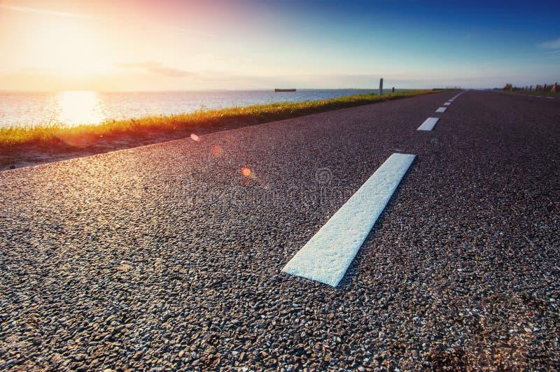 Estrada asfaltada ao longo do mar no por do sol foto de stock royalty free