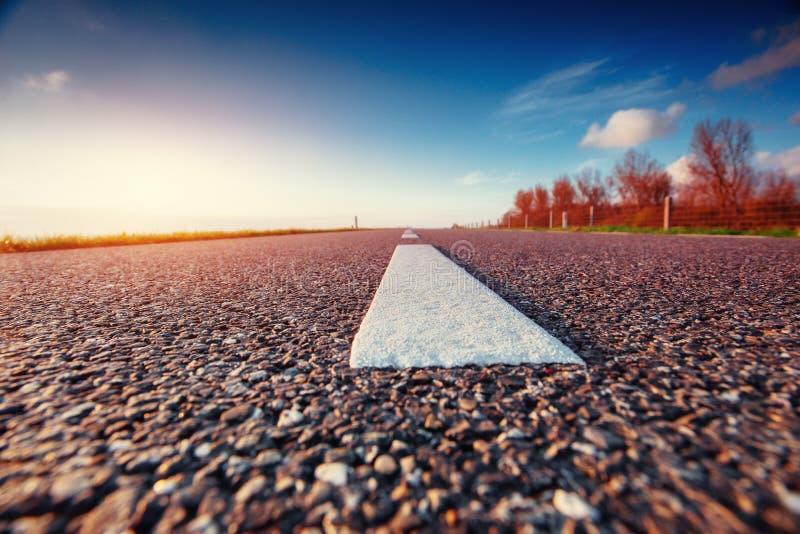 Estrada asfaltada ao longo do mar no por do sol imagem de stock royalty free