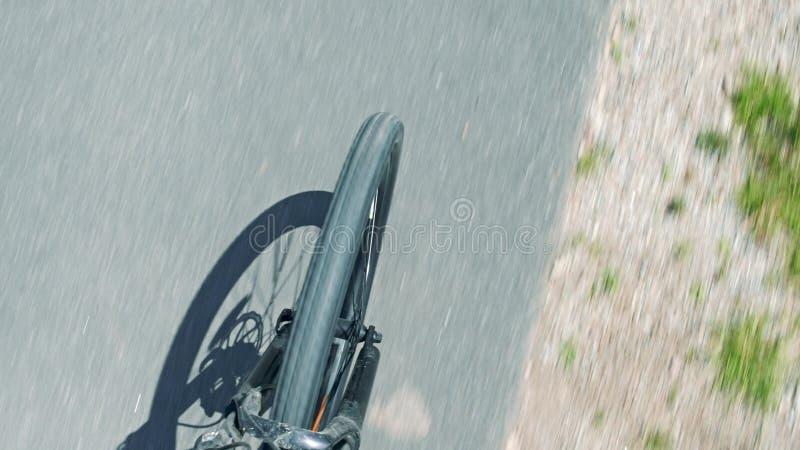 A estrada asfaltada borrada e a roda dianteira da bicicleta e a forquilha de giro, parte superior veem para baixo foto de stock royalty free