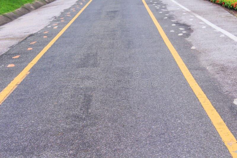 Estrada asfaltada com duas linhas amarelas e marcas do passeio imagem de stock