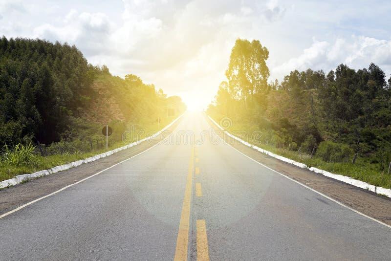 Estrada asfaltada com em linha reta com luz solar fotografia de stock