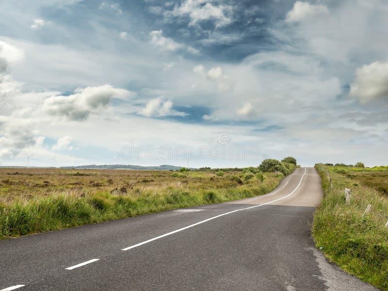 A estrada asfaltada com superfície nova e velha, céu colorido azul campos verdes imagem de stock royalty free