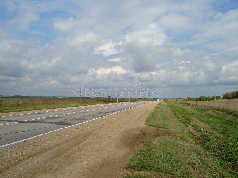 Estrada asfaltada direta através do campo sob o céu, em que as nuvens flutuam fotos de stock royalty free