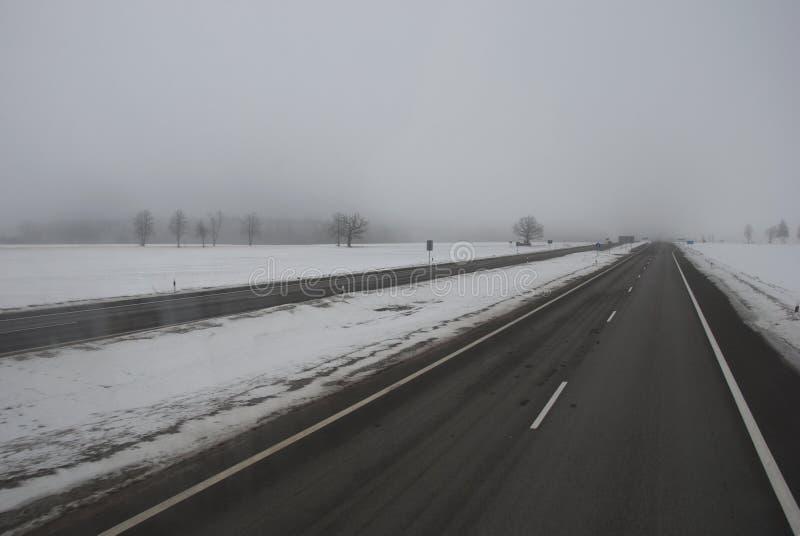 Estrada asfaltada do inverno e névoa da manhã imagem de stock