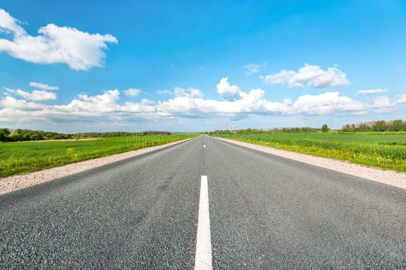 Estrada asfaltada em campos verdes no fundo azul do céu nebuloso imagem de stock