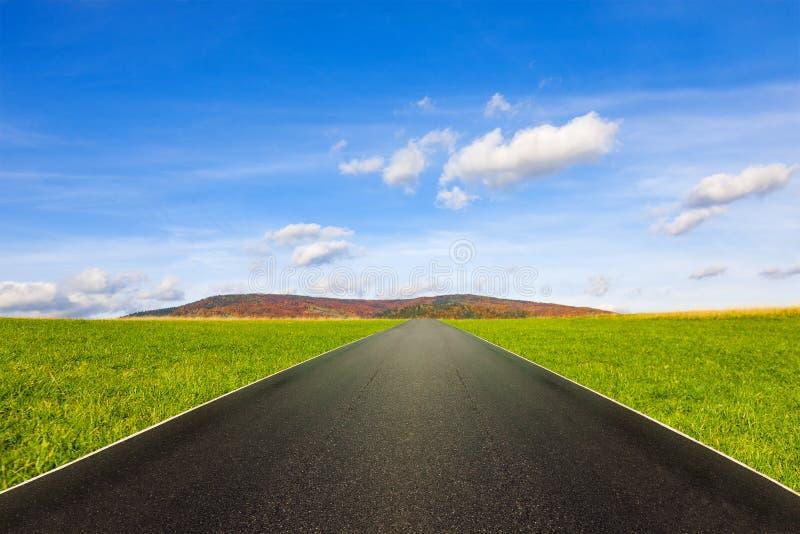 Estrada asfaltada entre o prado verde sob o céu azul com nuvens imagem de stock