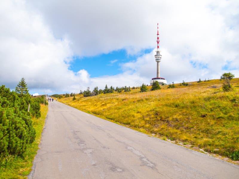A estrada asfaltada que conduzem ao transmissor da tevê e a vigia elevam-se na cimeira da montanha de Praded, Hruby Jesenik, Repú fotografia de stock