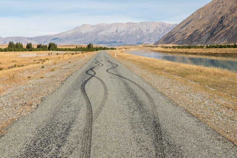 Estrada asfaltada rural com marcas de derrapagem pretas do pneumático fotografia de stock royalty free