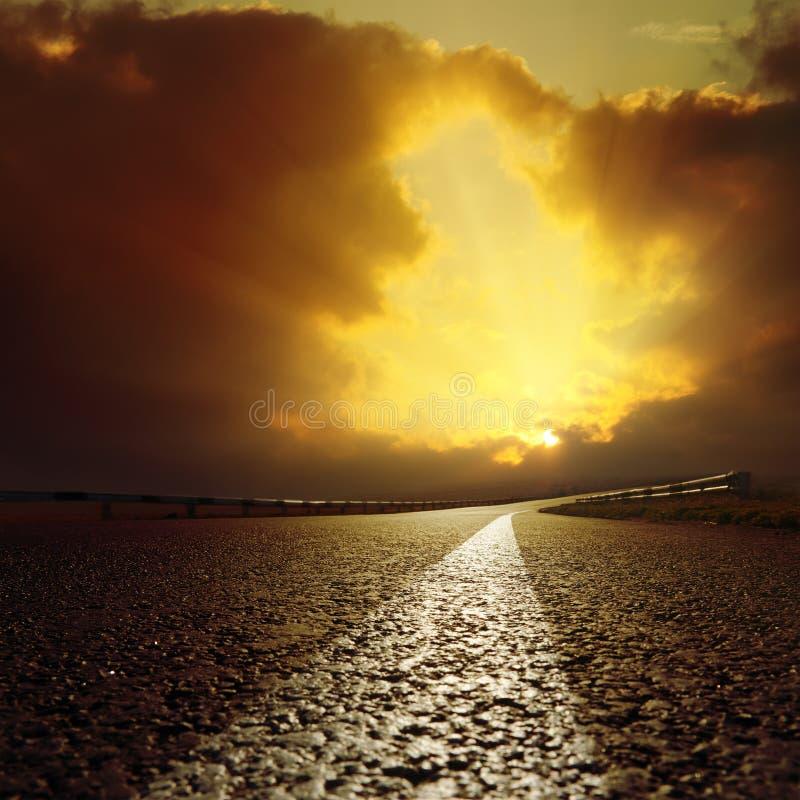 A estrada asfaltada vai iluminar-se nas nuvens fotografia de stock royalty free