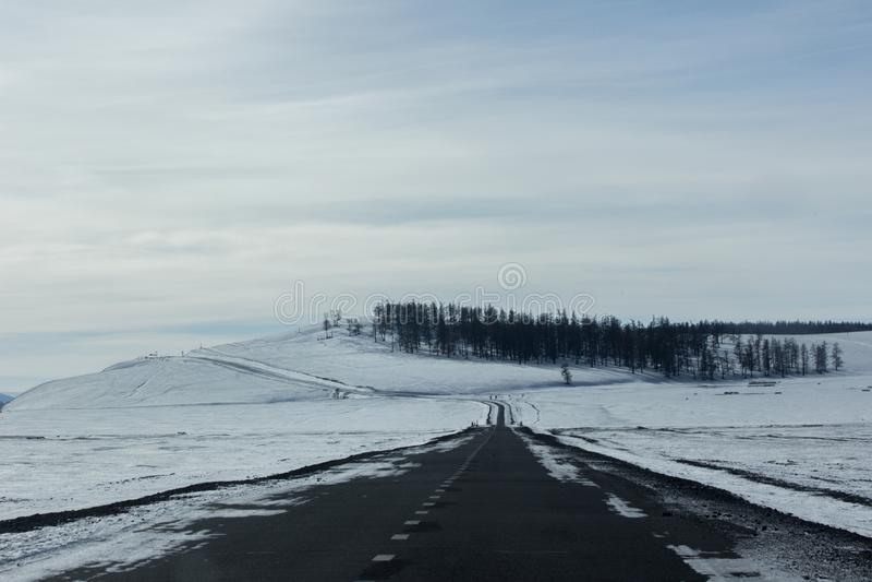 Estrada asfaltada vazia da curva com monte pequeno e árvore no inverno imagens de stock