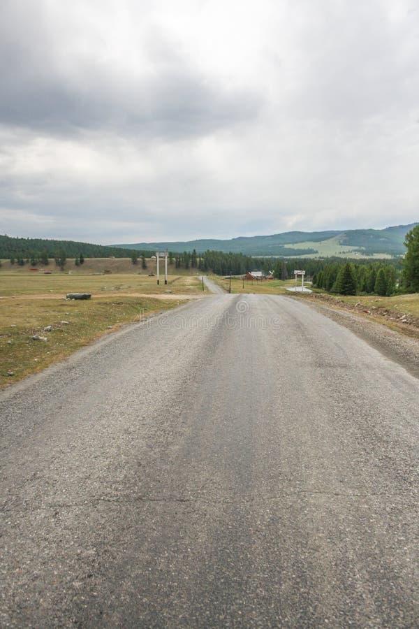Estrada asfaltada vazia que conduz às montanhas imagens de stock