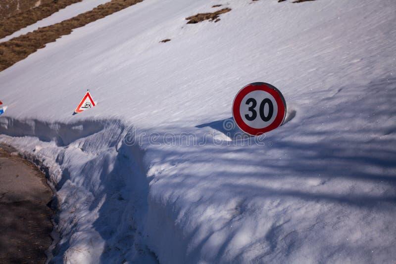 A estrada assina dentro a neve na estrada para chegar em Castelluccio di Norcia, Úmbria, Itália imagem de stock