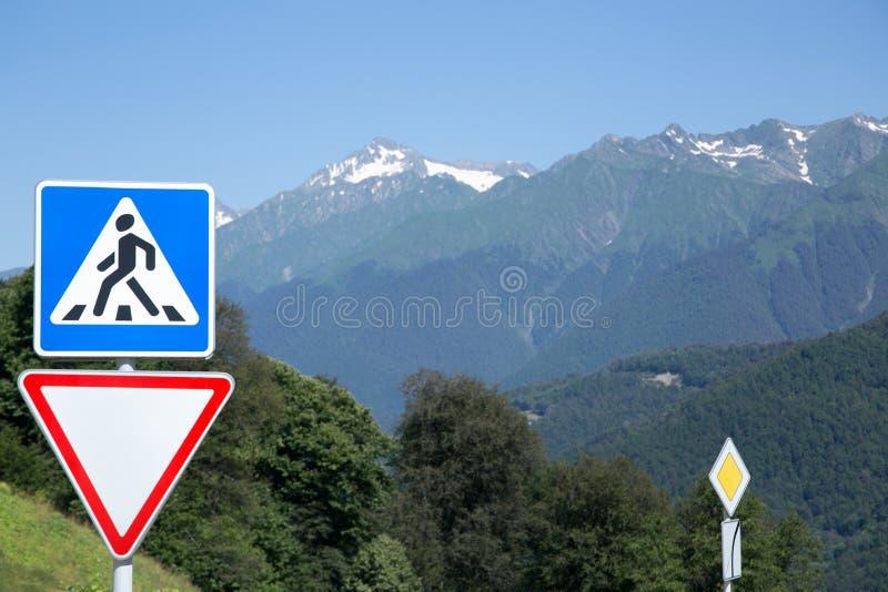 A estrada assina dentro uma paisagem da montanha O cruzamento pedestre, estrada leva, e do prioridade ` de Krasnaya Polyana do `  imagem de stock