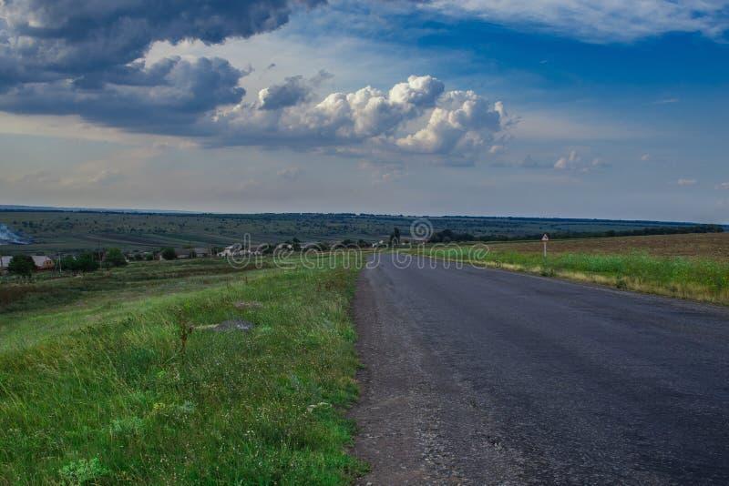 A estrada através do campo de grama velho com o céu azul nebuloso foto de stock royalty free