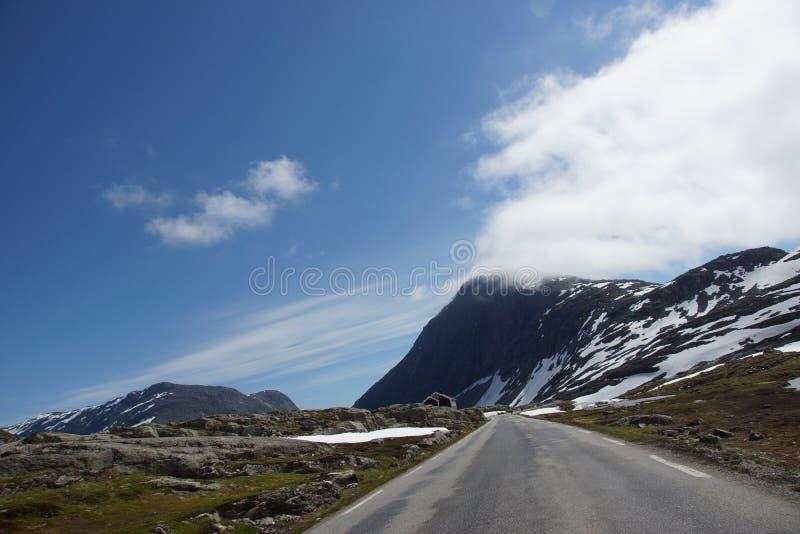 A estrada atravessa uma paisagem pitoresca da montanha em Noruega imagens de stock