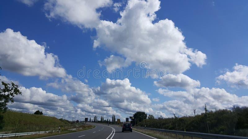 Estrada azul do céu nebuloso fotografia de stock royalty free