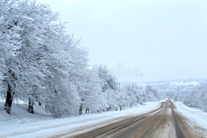 A estrada coberto de neve vai profundamente no país das maravilhas mágico do inverno da floresta Perigo que conduz na estrada Con imagem de stock