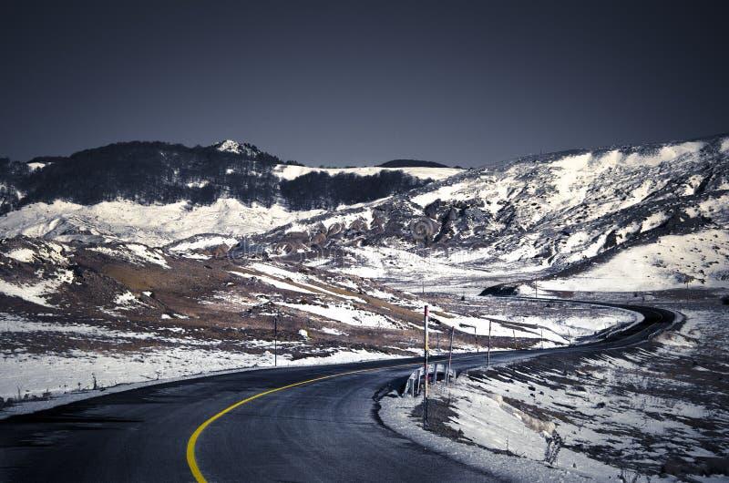Estrada com curvas em uma montanha com neve imagens de stock