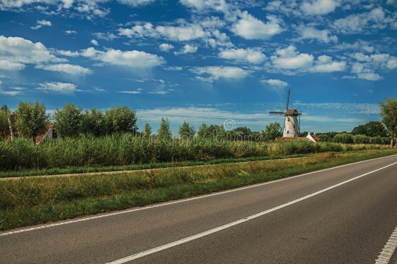 Estrada com moinho de vento velho e arbustos no fundo, no final da luz da tarde e do céu azul perto de Damme imagens de stock royalty free