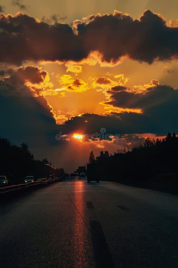 Estrada com os carros que viajam no por do sol Linha do horizonte com o sol e as nuvens de tempestade viagens Foco seletivo foto de stock royalty free