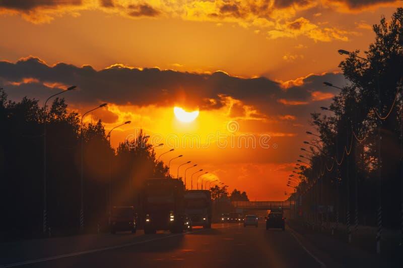 Estrada com os carros que viajam no por do sol Linha do horizonte com o sol e as nuvens de tempestade viagens Foco seletivo imagem de stock royalty free