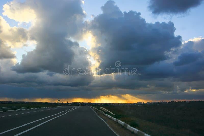 Estrada com os carros sob nuvens de tempestade no por do sol imagem de stock royalty free