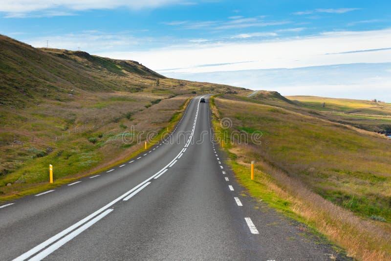 Estrada com a paisagem islandêsa sob um céu azul do verão. foto de stock