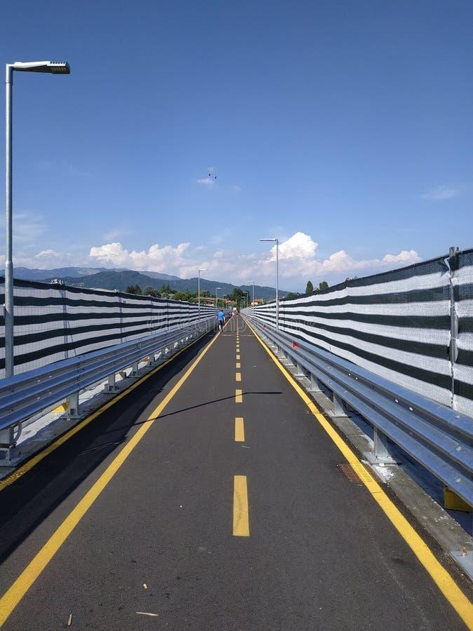 Estrada com sinais amarelos e claro infinitos - céu azul fotografia de stock royalty free