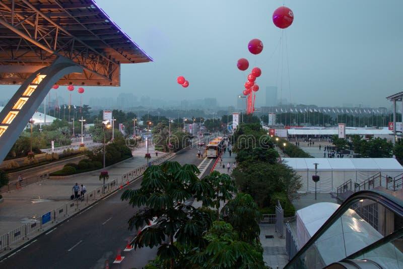 Estrada com transporte, passeios, palmeiras, barracas brancas Cidade grande moderna Bolas vermelhas do gel no ar fotografia de stock