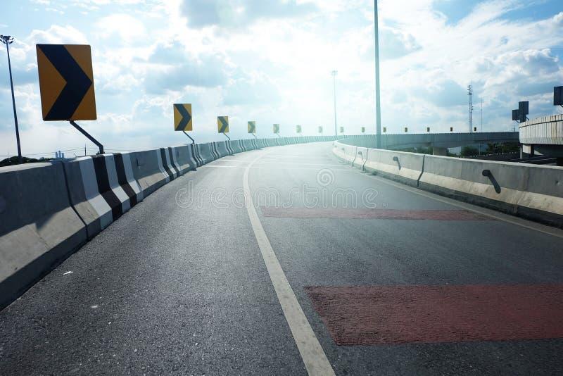 Estrada da estrada com sinal direito da volta ao céu imagem de stock